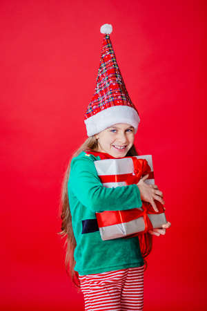 Merry Christmas, cunning happy attractive girl with gifts in a costume of Santa Claus helper elf on a bright red bright color background. Portrait of a beautiful elven baby. Copy space. 免版税图像 - 157539132