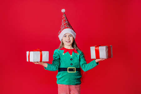 Merry Christmas, happy attractive girl with gifts in a costume of Santa Claus helper elf on a bright red bright color background. Portrait of a beautiful elven baby. Copy space. 免版税图像 - 157539136