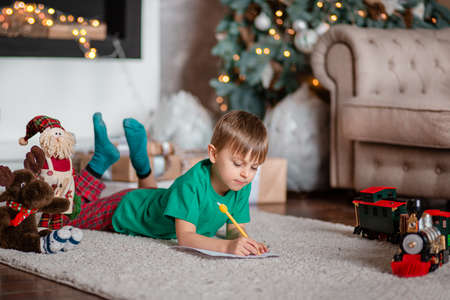 Cheerful boy is a letter to Santa, near the Christmas tree. Happy childhood, time for fulfilling wishes. Merry Christmas.