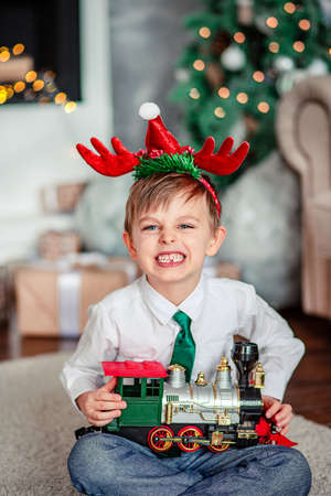 Angry upset little boy with a gift, toy train, under the Christmas tree on a New Year's morning. A time of miracles and fulfillment of desires. Merry Christmas. 免版税图像 - 157539229