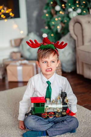Angry upset little boy with a gift, toy train, under the Christmas tree on a New Year's morning. A time of miracles and fulfillment of desires. Merry Christmas.