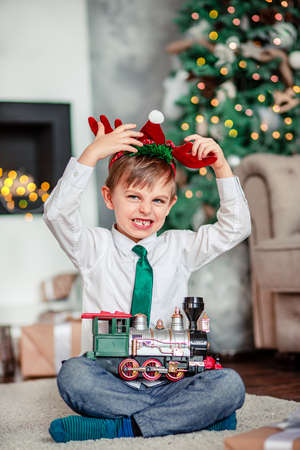 Angry upset little boy with a gift, toy train, under the Christmas tree on a New Year's morning. A time of miracles and fulfillment of desires. Merry Christmas. 免版税图像 - 157539233