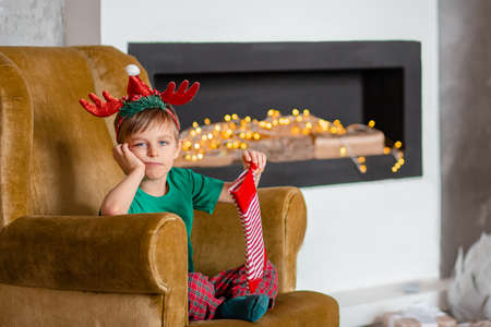 Cute boy waiting for a gift from Santa Claus, near the Christmas tree. Happy childhood, time to make wishes come true. Merry Christmas.