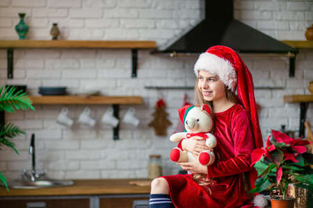 Merry Christmas. Cute little girl in Santa hat is holding a teddy bear sitting in the kitchen, waiting for the holiday. A time of miracles and fulfillment of desires.