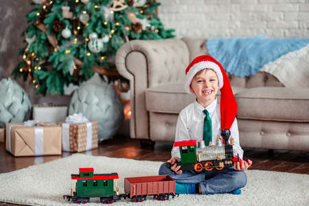 Good morning. Happy little boy with a gift, toy train, under the Christmas tree on a New Year's morning. A time of miracles and fulfillment of desires. Merry Christmas. 免版税图像 - 157539244