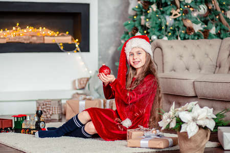 One cute cheerful girl santa hat near Christmas tree. Holds red christmas ball. Merry Christmas.
