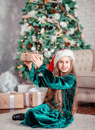 Little girl Santa Claus hat with gifts under Christmas tree sitting by the fireplace, unpacks gifts. Merry Christmas. 免版税图像