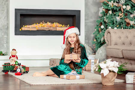 Little girl Santa Claus hat with gifts under Christmas tree sitting by the fireplace, unpacks gifts. Merry Christmas. 免版税图像 - 157539249