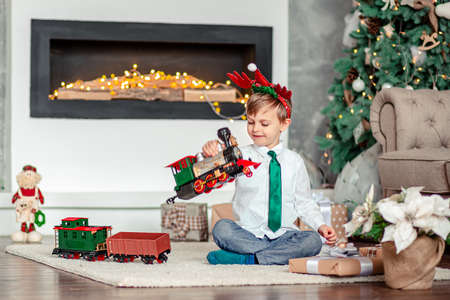Good morning. Happy little boy with a gift, toy train, under the Christmas tree on a New Year's morning. A time of miracles and fulfillment of desires. Merry Christmas. 免版税图像 - 157539327