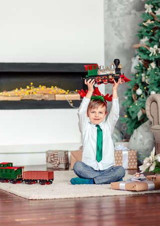 Good morning. Happy little boy with a gift, toy train, under the Christmas tree on a New Year's morning. A time of miracles and fulfillment of desires. Merry Christmas. 免版税图像