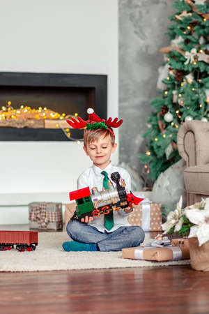 Good morning. Happy little boy with a gift, toy train, under the Christmas tree on a New Year's morning. A time of miracles and fulfillment of desires. Merry Christmas. 免版税图像 - 157539329