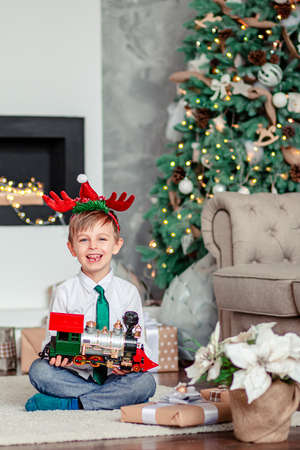 Good morning. Happy little boy with a gift, toy train, under the Christmas tree on a New Year's morning. A time of miracles and fulfillment of desires. Merry Christmas. Stock Photo