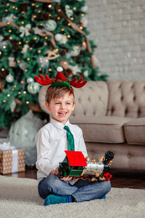 Good morning. Happy little boy with a gift, toy train, under the Christmas tree on a New Year's morning. A time of miracles and fulfillment of desires. Merry Christmas. 免版税图像 - 157539332