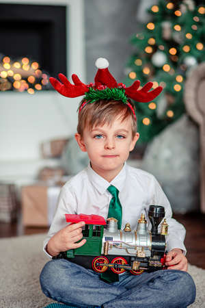 Good morning. Happy little boy with a gift, toy train, under the Christmas tree on a New Year's morning. A time of miracles and fulfillment of desires. Merry Christmas. Zdjęcie Seryjne