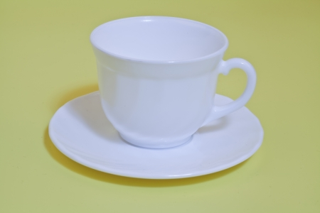 white cup with saucer on yellow