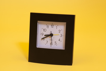 Table clock isolated on the yellow background  Stock Photo