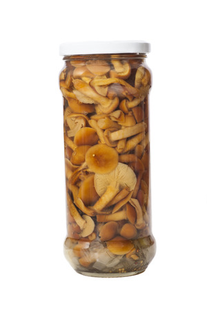 Glass jar of preserved mushrooms on a white background
