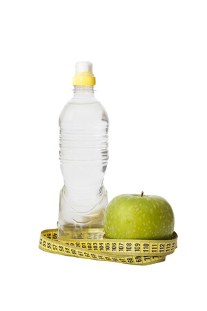 Green apple, bottled water and measuring tape isolated on white backgroun
