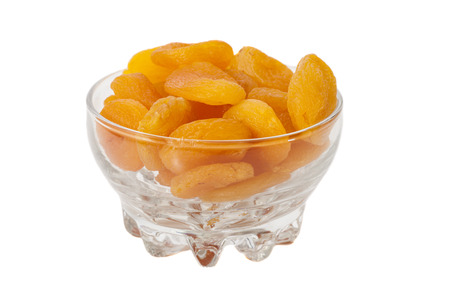 Dried apricots in glass bowl isolated on white  Stock Photo