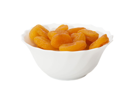 Dried apricots in  bowl isolated on white