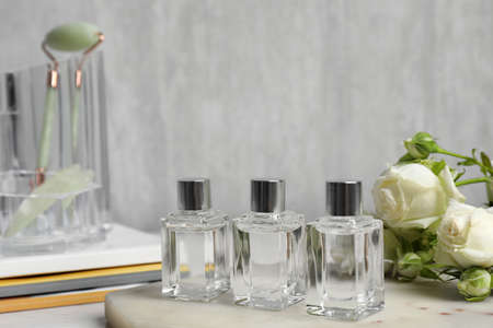 Perfumes and rose flowers on marble board Stock Photo