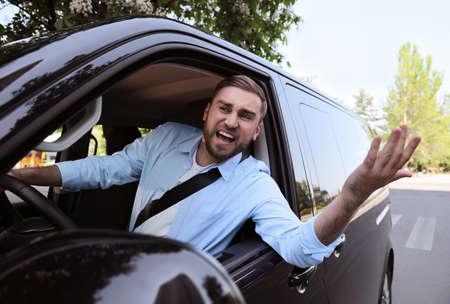 Emotional man in car. Aggressive driving behavior