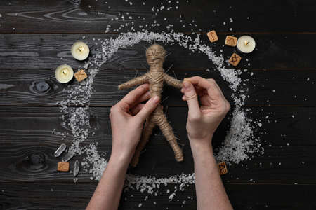 Woman stabbing voodoo doll with pins at wooden table, top view