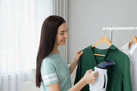 Woman steaming shirt on hanger at home Stockfoto