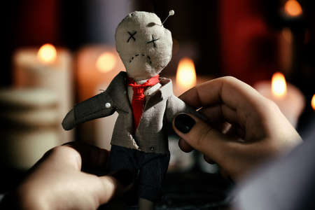 Woman holding voodoo doll with pins indoors, closeup. Curse ceremony