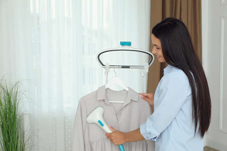 Woman steaming blouse on hanger at home. Space for text Stockfoto