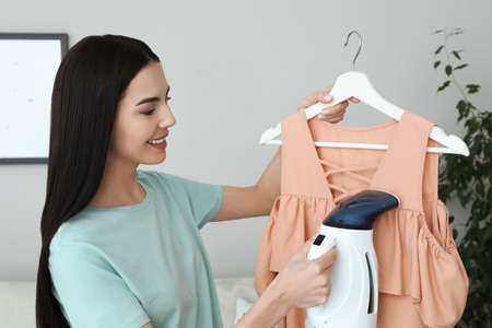 Woman steaming dress on hanger at home Stockfoto