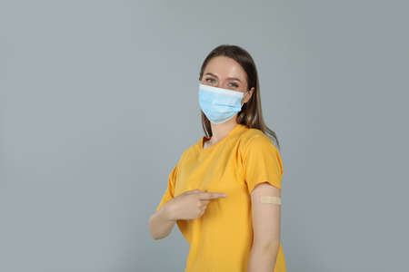 Vaccinated woman with protective mask showing medical plaster on her arm against gray background