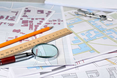 Office stationery and magnifying glass on cadastral maps of territory with buildings