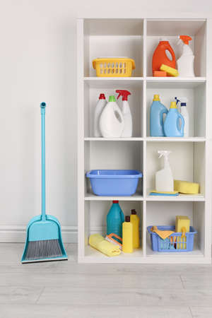 Shelving unit with detergents and cleaning tools near white wall indoors