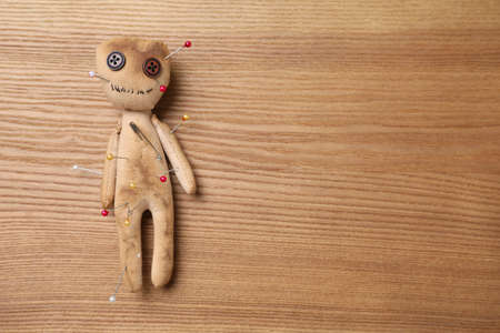 Voodoo doll pierced with pins on wooden table, top view. Space for text