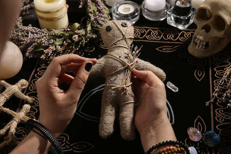 Woman stabbing voodoo doll with needle at table, closeup. Curse ceremony