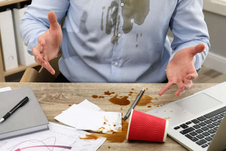 Man with spilled coffee over his workplace and shirt, closeup