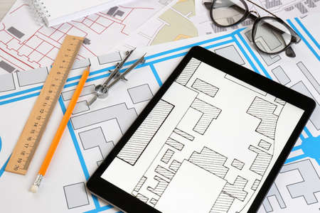 Office stationery, tablet and eyeglasses on cadastral maps of territory with buildings