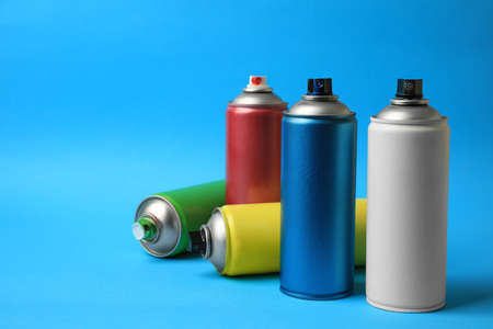 Cans of different graffiti spray paints on light blue background, space for text