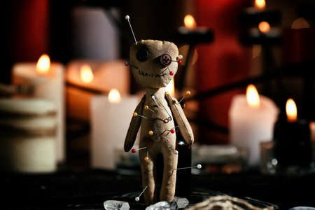 Voodoo doll pierced with pins on table in dark room. Curse ceremony