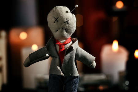 Voodoo doll pierced with pins in dark room, closeup. Curse ceremony Zdjęcie Seryjne