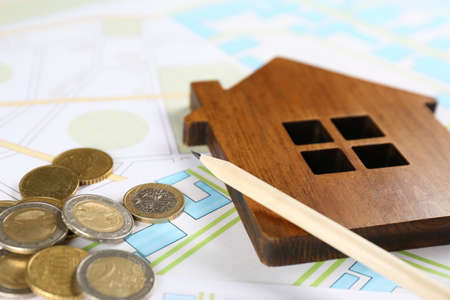 Coins, pencil and wooden house model on cadastral map, closeup Reklamní fotografie