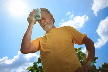 Senior man with towel suffering from heat stroke outdoors, low angle view Imagens