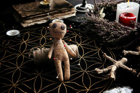 Voodoo doll pierced with pins on table. Curse ceremony