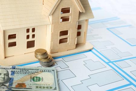 Money and house model on cadastral map, closeup Reklamní fotografie