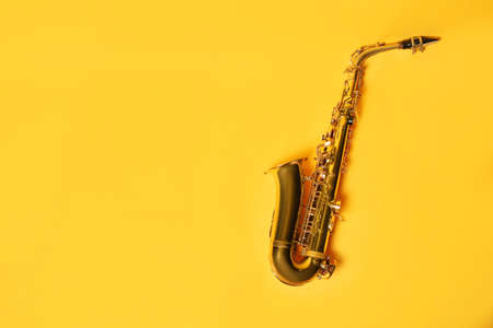 Beautiful saxophone on yellow background, top view. Space for text