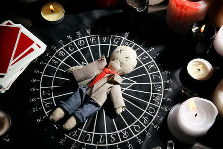 Voodoo doll pierced with needle surrounded by ceremonial items on table Zdjęcie Seryjne