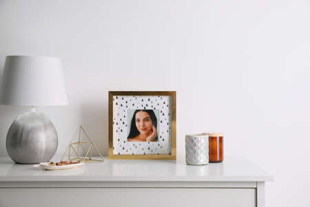 Photo frame with portrait of beautiful young woman near stylish decor on white table. Space for text