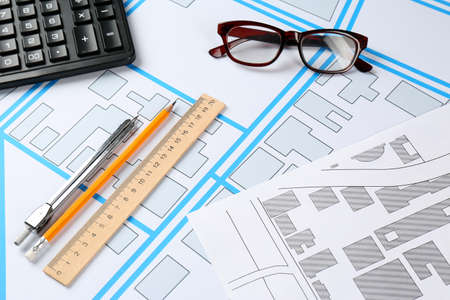 Office stationery and eyeglasses on cadastral maps of territory with buildings