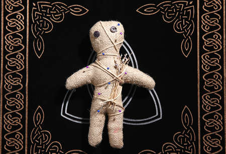 Voodoo doll pierced with pins on table, top view. Curse ceremony